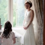 A blushing bride takes in her surroundings at Lords of the Manor's perfect Cotswold wedding venue.